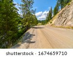 A rural dirt road with a steep mountain on one side and a ravine on the other in the mountains of the Coeur d