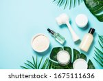 Small photo of Beauty product. Face massage brush, hyaluronic acid, cream for face, clay mask on blue background. Skin care concept. Flat lay image with copy space.