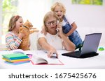 Small photo of Mother working from home with kids. Quarantine and closed school during coronavirus outbreak. Children make noise and disturb woman at work. Homeschooling and freelance job. Boy and girl playing.
