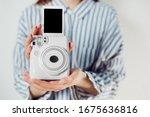 Instant Camera. Girl Holds...