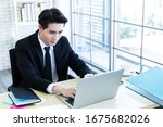 Small photo of Happy of asian young businessman see a successful business plan on the laptop computer and pen on wooden table background in office,business expressed confidence embolden