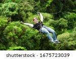 Small photo of zipline canopy zip line wire adventure jungle forest sport flight mature masculine pilgrim wearing informal linen on zipline or canopi experience in ecuadorian rain forest zipline canopy zip line wire