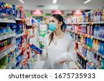 Small photo of Woman wearing protective mask preparing for virus pandemic spread quarantine.Hygiene, cleaning and disinfection products.Preventive measures and protection.Supply shopping during the epidemic.