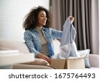 Small photo of Young curly hair satisfied happy african girl woman lady shopaholic customer sit on sofa unpack parcel delivery box look at clothes take out grey pullover sweater, online shopping shipment concept.