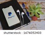 Small photo of Mexico City, Mexico - March 18, 2020; Paypal Apple Apps on Iphone Screen on a Black Book with Earphone Blue Pen and Succulent. PayPal is a worldwide online paypal payments. #paypal