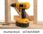 a yellow battery operated drill and construction screws in a residential construction framing setting isolated on white - stock photo