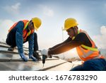 Construction worker wearing safety harness belt during working on roof structure of building on construction site,Roofer using air or pneumatic nail gun and installing concrete roof tile on top roof. - stock photo