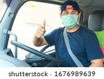 Small photo of Photos of Asian truck drivers wearing masks to protect against dust and the spread of COVID 19 in front of the car. Safety ideas for a worker in the transportation business. And is a new normal life.
