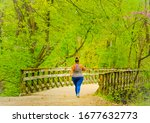 Small photo of Young African American woman walking briskly on wooden bridge on trail in spring; woman is overweight