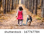 Stock photo little girl with dog walking on the road in forest back to camera 167767784