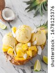 Small photo of pineapple coconut ice cream or sorbet pina colada scoops served in pineapple with slices of pineapple and coconut, ice cream or sorbet on a marble table