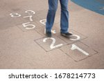 Teenager Playing Hopscotch On...