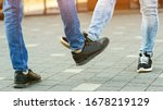 Small photo of Foot shake style of greetings. Prevention of fight against pandemic. Quarantine methods to control spread of coronavirus. New greeting style during coronavirus outbreak. People bump feet outdoors.