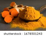 Small photo of Turmeric (curcumin) powder in a wooden ladle and fresh rhizome on a black background,For spices and medicine.