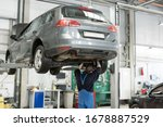 European mechanics in uniform is working in auto service with lifted vehicle. Car dealer repair and maintenance in the auto repair center. - stock photo