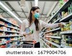 Small photo of Woman preparing for pathogen virus pandemic spread quarantine.Choosing nonperishable food essentials.Budget buying at a supply store.Pandemic quarantine preparation.Emergency to buy list