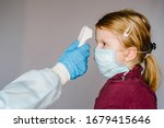 Coronavirus. Nurse or doctor checks girl's body temperature using infrared forehead thermometer (gun) for virus symptom - epidemic outbreak concept. High temperature. - stock photo