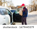 delivery man in protective mask and medical gloves holding a paper box. Delivery service under quarantine, disease outbreak, coronavirus covid-19 pandemic conditions. - stock photo