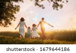 Small photo of Happy family on summer walk! Mother, father and daughters walking in the Park and enjoying the beautiful nature.