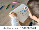 Small photo of Little kid with Stay Home draw. Coronavirus concept
