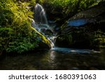 Beautiful waterfall in slow shutterspeed with morning sunlight in deep jungle.himachal india