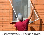 A worker is installing a window ...