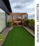 Small photo of A rooftop garden with beautiful plants, green grass carpet and wooden canopy just outside a glass doorway under cloudy sky in mid day