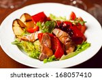 Succulent juicy portion of hot salad with grilled fillet steaks served with tomatoes, ruccola and roast vegetables on white plate. Haute cuisine concept. Indoor shot - stock photo