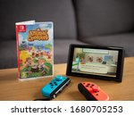 Small photo of UK, March 2020: Nintendo switch with joy con controllers and new animal crossing new horizons