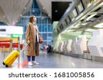 Woman with luggage stands at...