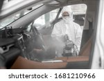 Disinfectant worker character in protective mask and suit sprays bacterial or virus in a car. - stock photo