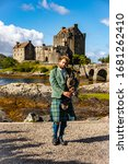 "Small photo of Dornie, SCOTLAND - Aug, 2018: Man dressed in typical clothes playing a ""Great Highlands Bagpipe"" in front of the Eilean Donan Castle"