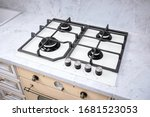 Small photo of Modern hob gas stove made of tempered white glass using natural gas or propane for cooking products on light countertop in kitchen interior.