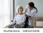 Small photo of Young woman doctor give help support handicapped old lady patient sitting in wheelchair, female caregiver or nurse assist take care of smiling senior disabled grandma, elderly healthcare concept
