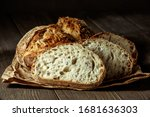 Small photo of Bread, traditional sourdough bread cut into slices on a rustic wooden background. Concept of traditional leavened bread baking methods. Healthy food.