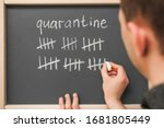 Small photo of inscription quarantine on a blackboard with chalk. strikethrough strikethrough. count days, cross out days