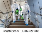 People wearing protective suits disinfecting stairs with spray chemicals to prevent the spreading of the coronavirus - stock photo
