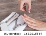 Small photo of Do yourself a manicure. Trim the nails on the hand. Shorten long nails. Home nail care, Spa, beauty. Manicure tools on a white towel. Procedure, nail salon. Tweezers, nippers, pusher, orange stick of