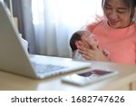 Small photo of businesswoman parenting a little baby newborn in business home office, mother using hand help her son belch burping after breastfeeding milk