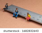 Small photo of Miniature figures sit on a metal rule or ruler demonstrating the concept of social distancing to avoid transmission of the corona virus or other contagious illness