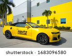 Small photo of ESTERO, FL -30 JAN 2020- View of a yellow Hertz rental car in front of the Hertz Arena, a multipurpose arena located in Estero, Florida, United States, near Fort Myers.