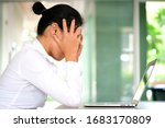 Small photo of woman sitting down, his face unsettled. At the computer desk she has headaches and stress. Cause of hard work and insufficient rest.