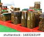 Small photo of Homemade pickled caper in a jar.Pickled caper berries in jar isolated on bright background. Capers in a jar in the market. Pickled marinated capers.Maltese cuisine. Malta food
