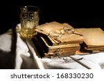 Aged book on white cloth with vintage glass - stock photo