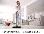 Young Woman Using Vacuum...