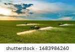 Small photo of Monte Alegre de Minas, Minas Gerais, Brazil, February 27, 2020: Agricultural sprayers making application at the end of the day with beautiful sunset, blue sky with clouds