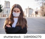 Small photo of Unhappy cranky frustrated sick girl, brunette woman wearing surgery medical mask with arms crossed feeling bad, ill, being hit by coronavirus, Covid2019 standing outdoors in city looking at you camera