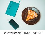 A book, a cell phone and a piece of pizz on a white table