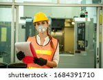 Female Mechanic wearing  protective mask to Protect Against Covid-19,Female technician worker working and checking machine in a large industrial factory,Coronavirus has turned into a global emergency - stock photo