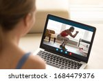 Small photo of Focus on laptop screen with young woman in sportswear doing morning exercises, deep squats on yoga mat, staying fit at home. Interested girl watching online educational fitness workshop training.